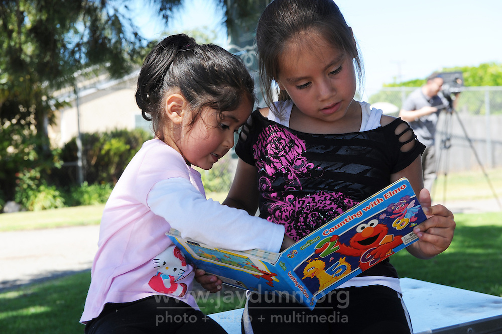 """Six-year old Cloy Rosas, right, reads with a friend after """"checking out"""" a Sesame Street book on opening day of Salinas' first Little Library at El Gabilan Park in Salinas. Two more Little Libraries were installed on Wednesday, in Central Park and McKinnon Park, with two more slated to start this summer."""