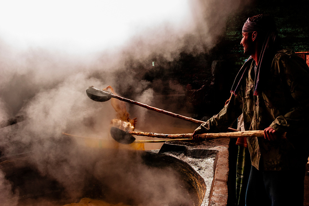 Men making molasses in steamy vats in a small factory near Dendara, Egypt