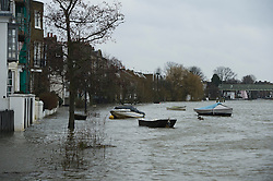 © London News Pictures. 31/01/2014. Boats float next to properties where flood water covers the Thames Path riverbank at Strand-on-the-Green in Chiswick, West London, where the rRiver Thames has broken it's banks. Photo credit: Ben Cawthra/LNP