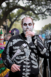 04 March 2014. New Orleans, Louisiana.<br /> Fat Tuesday. Mardi Gras Day. The Skeleton Krewe gather before dawn and take the long walk through back streets onto St Charles Avenue from Uptown to Downtown New Orleans.<br /> Photo; Charlie Varley/varleypix.com
