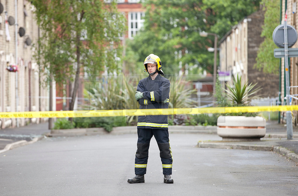 © Licensed to London News Pictures. 27/06/2012. Oldham , UK . A large explosion , believed to be caused by gas , has brought down at least one house in an Oldham terrace. A lone fireman stands behind a tape barrier . Photo credit : Joel Goodman/LNP