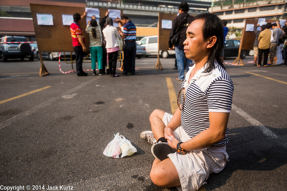 26 JANUARY 2014 - BANGKOK, THAILAND: A man who came to vote but was unable to meditates in front of the voting booths at Wat That Thong after the polling place was shutdown by anti-government protestors. Anti-government protestors forced the closure of polling places in Bangkok Sunday as a part of Shutdown Bangkok. Early voting was supposed to be Sunday January 26 but blocked polling places left hundreds of thousands of people unable to vote casting the February 2 general election into doubt and further gridlocking Thai politics. Protestors blocked access to gates and entry ways to polling places and election officials chose the close them rather than confront protestors. Shutdown Bangkok has been going for 12 days with no resolution in sight. Suthep, the leader of the anti-government protests and the People's Democratic Reform Committee (PDRC), the umbrella organization of the protests,  is still demanding the caretaker government of Prime Minister Yingluck Shinawatra resign, the PM says she won't resign and intends to go ahead with the election.    PHOTO BY JACK KURTZ