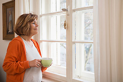 Side profile of a senior woman having cup of tea looking through window at home, Munich, Bavaria, Germany