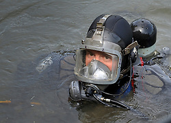 © licensed to London News Pictures. RICHMOND, UK.  01/08/11. A police diver emerges from the water. The Metropolitan police search the River Thames near Richmond, London, today (1 Aug 2011) after a 17 year boy went missing after taking part in a kayak competition.  Mandatory Credit Stephen Simpson/LNP