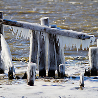 Pilings along Fort Hancock near Sandy Hook Bay covered in ice on a frigid winters day.