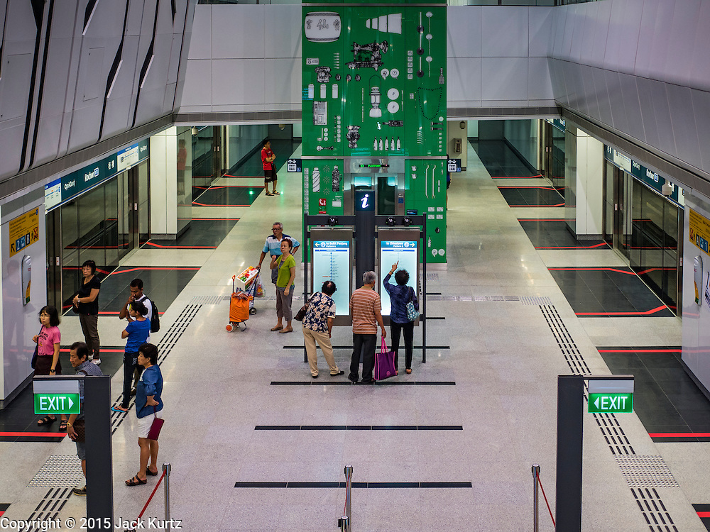 """27 DECEMBER 2015 - SINGAPORE, SINGAPORE:  People look at subway schedules in the Rochor subway station in the Little India section of Singapore on the first day the station was open. Singapore opened the extension of the Downtown Line on its subway system Sunday. The extension is a part of Singapore's plans to make the city-state a """"car lite"""" metropolis with plans to double the current subway to more than 360 kilometers of track by 2030. The government plans to have 80% of homes within a 10 minute walk of a subway station.   PHOTO BY JACK KURTZ"""