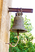 Bronze bell hangs on a wall at Agia Triada Monastery or the Monastery of Agia Triada Tsangarolon is a Greek Orthodox monastery in the Akrotiri peninsula in the Chania regional unit, Crete, Greece.