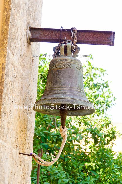 Bronze bell hangs on a wall at Agia Triada Monastery or the Monastery of Agia Triada Tsangarolon is a Greek Orthodox monastery in the Akrotiri peninsula in the Chania regional unit, Crete, Greece.