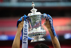 The FA cup trophy is lifted into the air