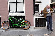 Een man verstuurt een SMS terwijl hij wacht bij de Oudegracht in Utrecht naast een cruisebike.<br /> <br /> A man is sending a text message while waiting next to a cruiser bike.