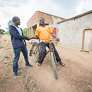 CAPTION: Jean Claude's first step into enterprise development was to buy a bicycle like this one that he could operate as a taxi. He still has friends in the trade. When he received his initial cash transfers, he set aside FRW 5,000 (€ 6.50) each month to take care of rent and other household expenses. Riding the bicycle taxi, he made FRW 20,000 per month, which helped him and Claudine to quickly stabilise at home. It also left him with additional funds beyond this, which allowed him to save, putting aside cash for a motorcycle driving course, license and eventually the bike itself (for which he took a loan to ease payment). LOCATION: Kabuga Village, Gafumba Cell, Rusatira Sector, Huye District, South Province, Rwanda. INDIVIDUAL(S) PHOTOGRAPHED: Jean Claude Minani (left) and Joseph Habineza (right).