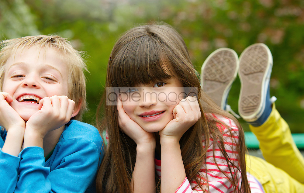 Boy and Girl Lying Side by Side Outdoors