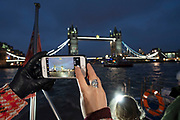 Tourist takes a photograph on her mobile phone of Tower Bridge at night while on a river taxi boat in London, United Kingdom.