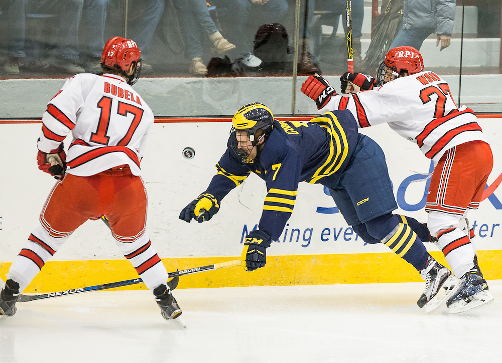 University of Michigan Forward JT Compher (7) is checked by Rensselaer Polytechnic Institute Forward Jake Wood (27) during a NCAA Division I hockey game between Rensselaer Polytechnic Institute and the University of Michigan at Houston Field House on October 24, 2015 in Troy, New York. (Dustin Satloff)