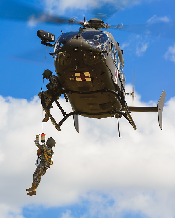 A flight medic signals to the firefighter during hoist operations.