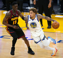 Mar 26, 2021; San Francisco, California, USA; Golden State Warriors forward Kelly Oubre Jr. (12) drives past Atlanta Hawks guard Tony Snell (19) during the second quarter of an NBA basketball game at Chase Center. Mandatory Credit: D. Ross Cameron-USA TODAY Sports