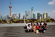 Visitors have their photographs taken on the Bund with a view of Pudong's modern Lujiazui Financial District across the Huangpu River in Shanghai, China on 05 September, 2011. The Bund and the skyscrapers of Pudong are the most famous and iconic sites of Shanghai.