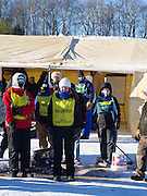 Volunteers stay warm before a fire, prior to the Apostle Islands Sled Dog Races. Scenes from the Apostle Islands Sled Dog Race, hosted by the Bayfield Chamber of Commerce, near Bayfield, WI