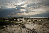 Sunbeams stream from broken clouds above the dunes of the Provincelands area of the Cape Cod National Seashore.