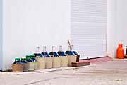 Demi johns in plastic baskets filled with wine standing outside the winery. Hercegovina Produkt winery, Citluk, near Mostar. Federation Bosne i Hercegovine. Bosnia Herzegovina, Europe.