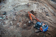 An excavator removing earth from a building site outside Coventry train station on the 28th of April 2021, Coventry, United Kingdom. The train station in Coventry is currently being redeveloped as part of an £82 million project for the Coventry UK City of Culture 2021.