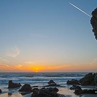 As the sun sets, a jet flies high above Panther Beach, near Santa Cruz, California.