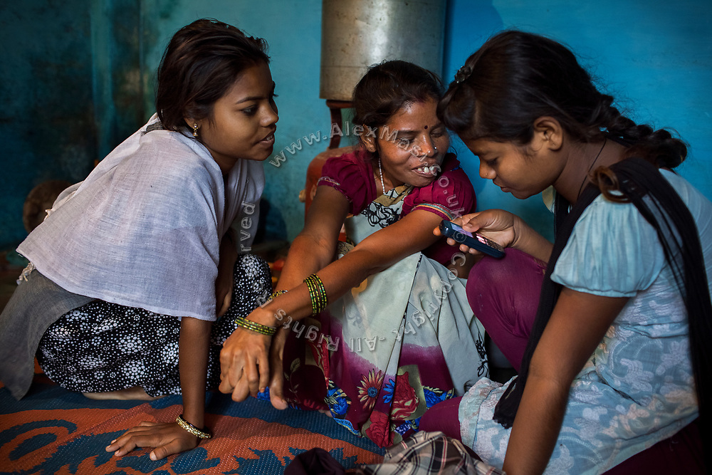 Poonam, 13, (right) is playing with the family's mobile phone next to her oldest sister Arti, 19, (left) and their mother, Sangita, 42, while sitting on the floor of their newly built home in Oriya Basti, one of the water-contaminated colonies in Bhopal, central India, near the abandoned Union Carbide (now DOW Chemical) industrial complex, site of the infamous '1984 Gas Disaster'.