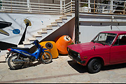 Colourful Greek scene of a red pick up truck, a motorbike and two buoys in Kioni, Ithaca, Greece. Ithaca, Ithaki or Ithaka is a Greek island located in the Ionian Sea to the west of continental Greece. Ithacas main island has an area of 96 square kilometres. It is the second-smallest of seven main Ionian Islands.