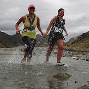 Runner Olivia Caldwell (right) and friend cross Moke Creek on the Ben Lomond High Country Station during the Pure South Shotover Moonlight Mountain Marathon and trail runs. Moke Lake, Queenstown, New Zealand. 4th February 2012. Photo Tim Clayton