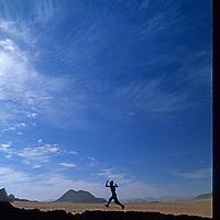 A woman runs through rough terrain in Jordan's Wadi Rum, near the edge of the Arabian Desert.