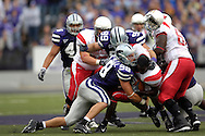 Kansas State defenders Ian Campbell (98) and Steven Cline (99) pop Illinois State running back Pierre Rembert (5) as he loses his helmet in the first half, at Bill Snyder Family Stadium in Manhattan, Kansas, September 2, 2006.  The Wildcats beat the Redbirds 24-23.