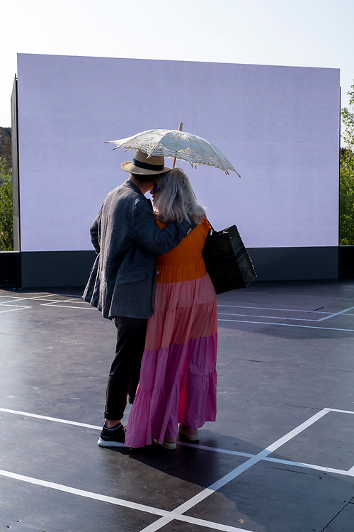 A couple pause under a parasol on a summers evening on Beautiful Sunday, a sculptural installation by the artist Jacqueline Donachie that celebrates 'all the dance floors of Folkestone' by marking out their size one-to-one on a huge stage set in the middle of the derelict gasworks site. Visitors are invited to stand on the stage and remember (if they are local residents) the dance floors - many of which are no longer active on the 21st of July 2021, in Folkestone, United Kingdom. The artwork is part of the Creative Folkestone Triennial 2020, The Plot, which sees 27 newly commissioned artworks appearing around the south coast seaside town. The new work builds on the work from previous triennials making Folkestone the biggest urban outdoor contemporary art exhibition in the UK. (photo by Andrew Aitchison / In pictures via Getty Images)