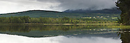 Cairngorm Mountains and Abernethy Forest reflected in the surface of Lock Garten near Boat of Garten, Cairngorms National Park, Scotland, Uk