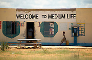 Namibia, Africa, 2004 - A humorous and profound sign names a general store in the remote area near Ruacana in the far north at the Angolan border. The store also hosts a simple radio telephone the only type of phone in this remote region.