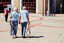 A couple hold hands as they walk through Basildon Town Centre. Essex