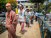 22 JULY 2015 - BANGKOK, THAILAND:  DADODIN PATAVATTO, a Buddhist monk, leads a silent march around Government House, which is the office of the Prime Minister in Bangkok. More than 100 people from Krabi province, members of the Save Andaman from Coal Network (SACN) have staged a series of marches and sit-ins outside the Prime Minister's office. They are opposed to plans to build an 800 megawatt coal fired power plant near southern Thailand's Andaman coast about 650 kilometers (400 miles) south of Bangkok. The area is famous for its pristine beaches. Residents worry that the coal fired power plant will pollute the area and send power to Bangkok.    PHOTO BY JACK KURTZ