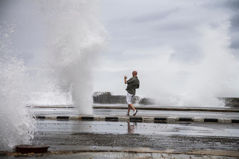 Tourist capturing sea water shooting up through manholes during storm, Havana, Cuba