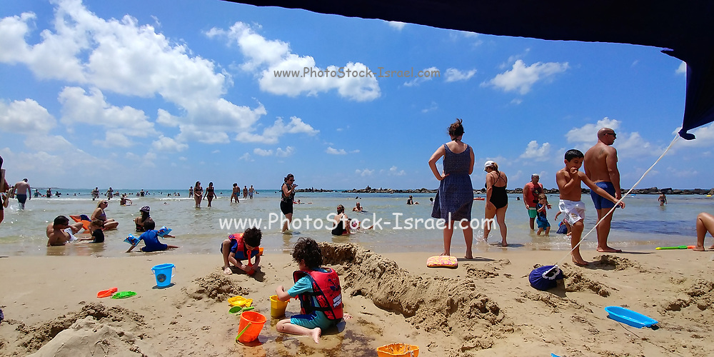 Families at a day of leisure on a sandy Mediterranean beach. Photographed in Haifa, Israel