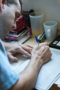 A prisoner writing a letter to his family at his cell desk. HMP/YOI Portland, Dorset. A resettlement prison with a capacity for 530 prisoners. Dorset, United Kingdom.