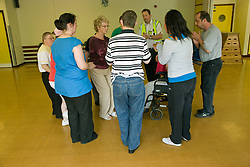 Day Service users with learning disability taking part in line dancing class with a Care Assistants and Duty Service Officer joining in the activity,
