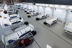 © Licensed to London News Pictures. 12/04/2020. Manchester, UK. The first patient bays to be populated with beds are checked and cleaned . The National Health Service is building a 648 bed field hospital for the treatment of Covid-19 patients , at the historical railway station terminus which now forms the main hall of the Manchester Central Convention Centre . The facility is due to open on Easter Monday , 13th April 2020 , and will treat patients from across the North West of England , providing them with general medical care and oxygen therapy after discharge from Intensive Care Units . Photo credit: Joel Goodman/LNP