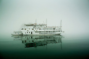 04 APRIL 2012 - HA LONG, VIETNAM:   A tourist cruise ship in the fog in Ha Long Bay. In 1994 UNESCO declared 174 square miles of Ha Long Bay a World Heritage Site. There are nearly 2000 distinct rock islands in the bay, which for centuries has been the home to isolated fishing villages. Now thousands of tourists stream through the bay and around the islands every day on cruise ships. On the Vietnamese mainland, around the town of Ha Long, real estate companies are developing exclusive condominium and apartment complexes for use as weekend homes for people in Hanoi, about a 3.5 hour drive from Ha Long.      PHOTO BY JACK KURTZ