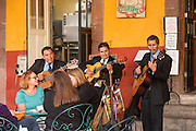 A Mexican mariachi band plays for dinners at a cafe in the Jardin square January 6, 2016 in San Miguel de Allende, Mexico.