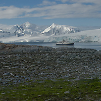 The National Geographic Endeavor anchors in a cove near Damoy Point on Wiencke Island, Antarctica.  Behind is the Neumeyer channel and mountains on Anvers Island.