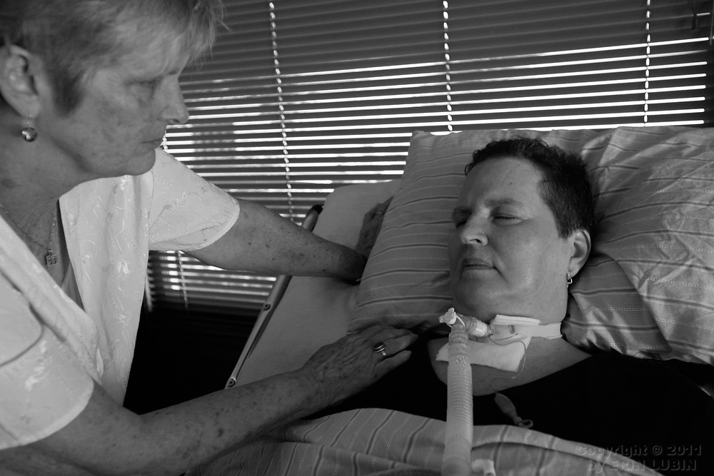 Karen Jorgensen ended her life in July of 2007 after five years of slow debilitation brought on by Amyotrophic Lateral Sclerosis, ALS or, Lou Gehrig's disease. The photos in this gallery are of Jorgensen's life with her partner, Karen Toloui, during the years they lived with the fatal illness. Jorgensen's family buried her ashes at a cemetery in Berkeley, CA in January of 2008...Toloui checks in with Jorgensen before friends and family arrive for  a live memorial at Jorgensen's home on July 14, 2007, three days before Jorgensen would have her breathing assist machine turned off for good...Photographs by Erin Lubin