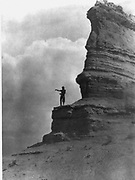Barechested Tewa man, standing high on a cliff, arms stretched before him as he sprinkles cornmeal as an offering at the start of a day. Perhaps to the sun, or some other deity, or to mundane daily events, 1927.  Photograph by Edward Curtis (1868-1952).