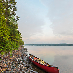 A canoe on the shore of Cross Lake at dawn in Square Lake Township, Maine.