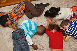Multiracial group of children playing dead