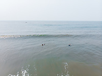 Aerial view of two surfers in the ocean on a sunny day at Agonda beach in south Goa, India.