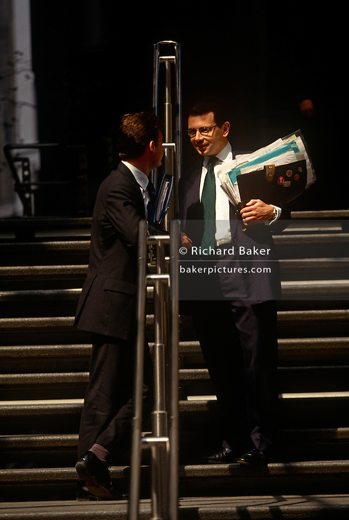 Businessmen in the insurance industry meet and talk outside the Lloyds of London address in the City of London